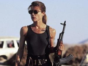 Sarah Connor stands in the sunset light, holding a gun.